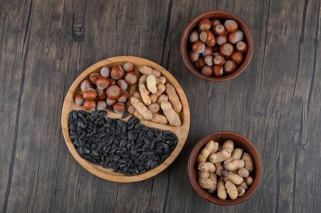 Tavola di legno piena di noci sane e semi di girasole neri.