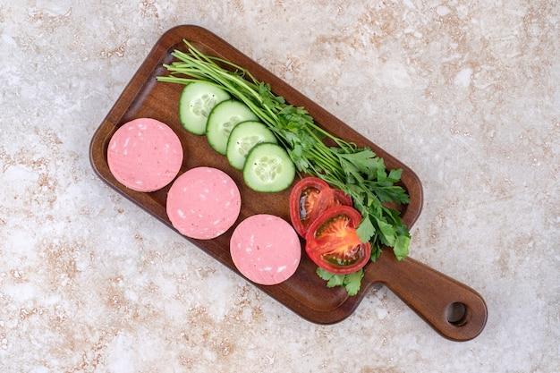 Una tavola di legno di salsiccia a fette e verdure tritate su una superficie di pietra.