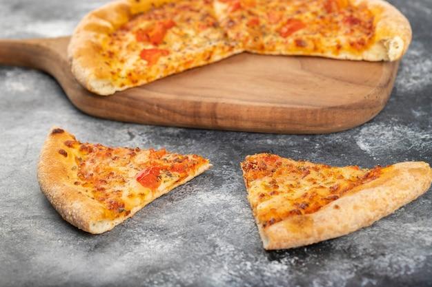 Tavola di legno di fette di pizza di pollo su sfondo di pietra.