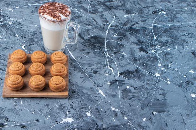 Una tavola di legno di biscotti rotondi dolci con una tazza di vetro di gustoso caffè caldo su uno sfondo di marmo.