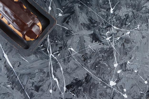 Una tavola di legno di gustoso eclair al cioccolato posto su uno sfondo di marmo.