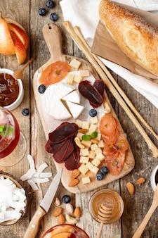 Tavola di legno con diversi tipi di formaggi, salumi, frutta, noci, baguette su una tavola di legno.stile rustico.french festa di degustazione.