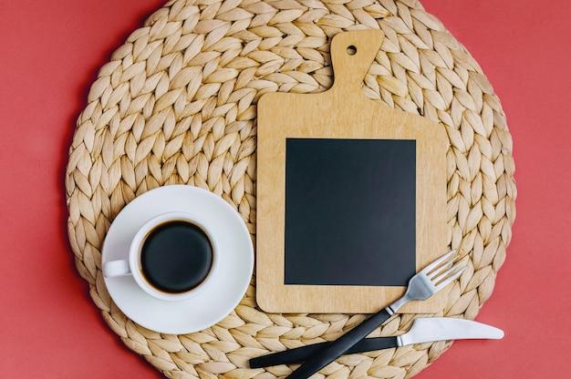 Tavola di legno con posto da inserire su uno sfondo rosa. utensili da cucina.