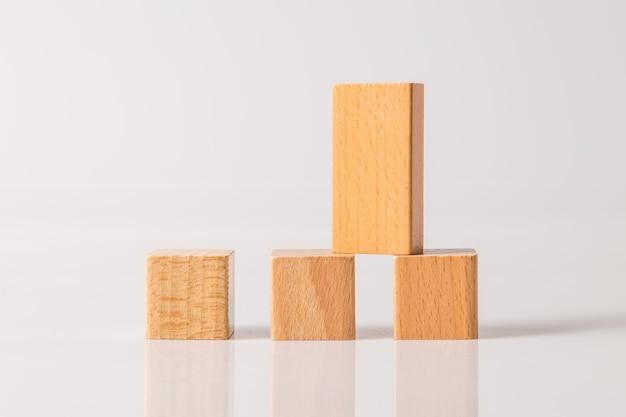 Tavola di legno sul cubo di forme geometriche in legno isolato su uno sfondo bianco