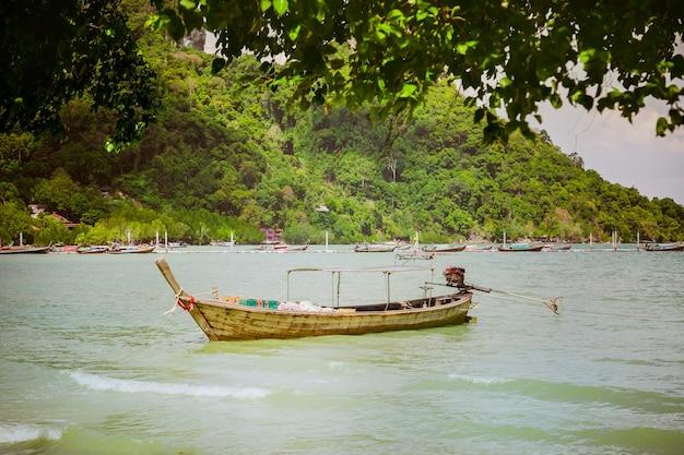 La barca di legno consegna i prodotti e le merci a terra problema dell'isola di rimozione dei rifiuti della consegna del cibo