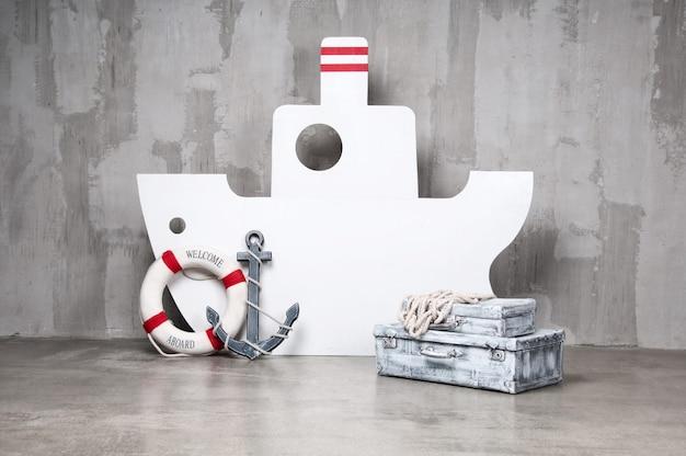 Barca di legno su uno sfondo grigio con un'ancora e un cerchio.