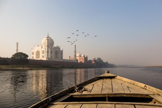 La barca di legno sul fiume di yamuna con taj mahal e l'uccello sorvolano.