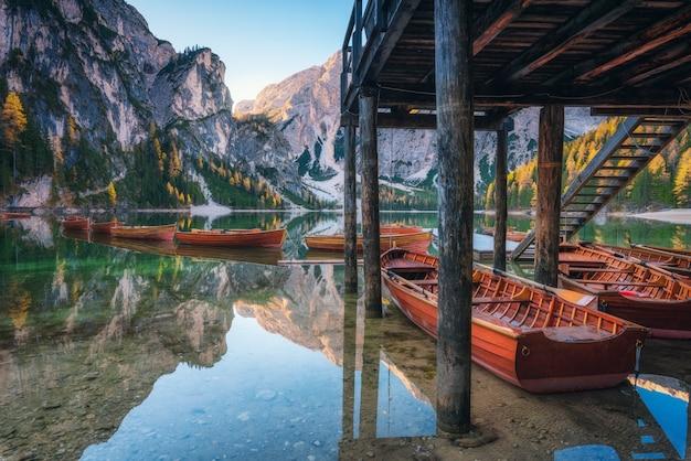 Barche di legno vicino alla casa nel lago braies ad alba in autunno