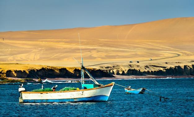 Barche di legno alla riserva nazionale di paracas nell'oceano pacifico in perù