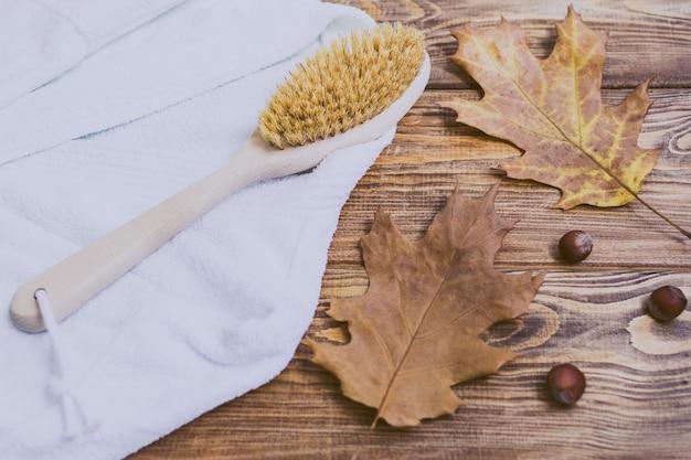 Spazzola per il corpo in legno, accappatoio, nocciole e foglie di autunno su un tavolo di legno