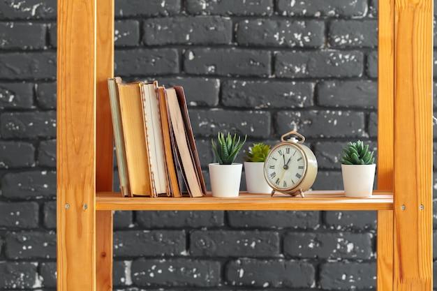 Scaffale per libri in legno con libri e roba contro il muro di mattoni neri