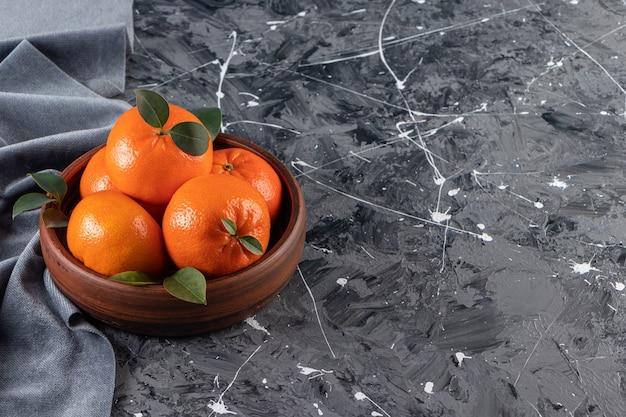 Ciotola di legno di arance fresche e succose sulla superficie in marmo