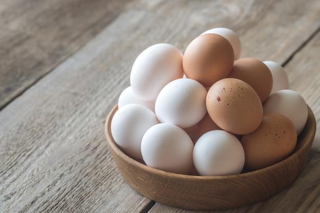 Ciotola di legno di uova di gallina crude