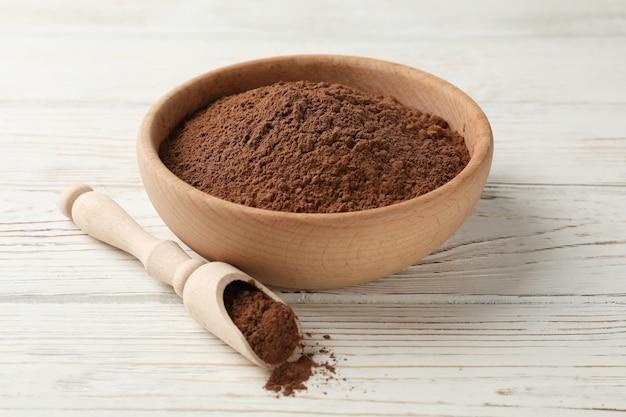 Ciotola e mestolo di legno con cacao in polvere su legno bianco, primo piano