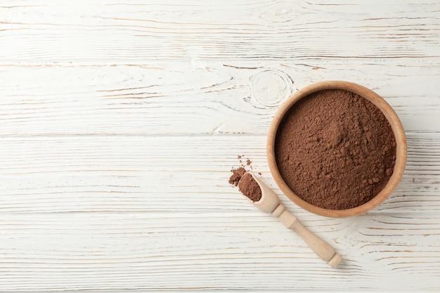 Ciotola e mestolo di legno con cacao in polvere su legno bianco, spazio per testo