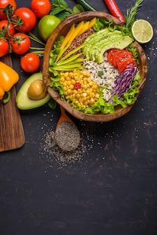 Ciotola di legno con ceci, avocado, riso selvatico, quinoa, peperone, pomodori, verdure, cavolo, lattuga sul tavolo di pietra scura e cucchiaio di legno con semi di chia. vista dall'alto con copyspace.