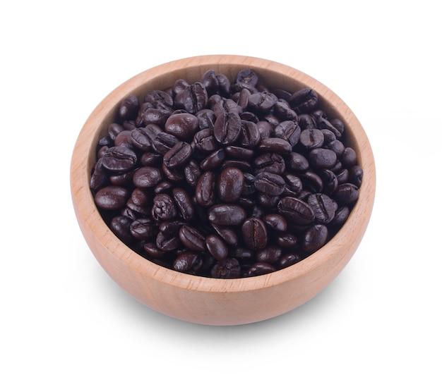 Ciotola di legno con chicchi di caffè e foglie di caffè su sfondo bianco.