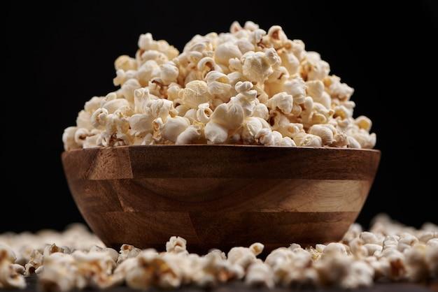 Ciotola di legno con popcorn salato su un tavolo di legno