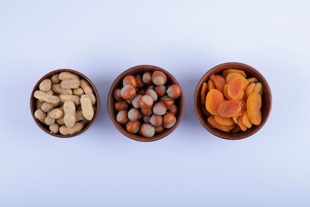 Ciotole di legno piene di arachidi non sbucciate, nocciole e albicocche secche su bianco.