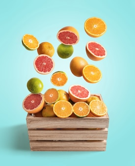Scatola di legno di arance assortite e mandarini volanti, isolato da sfondo blu con copia spazio