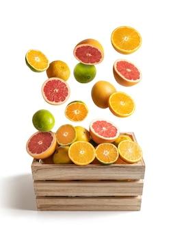 Scatola di legno di arance assortite e mandarini che volano, isolati dal bianco