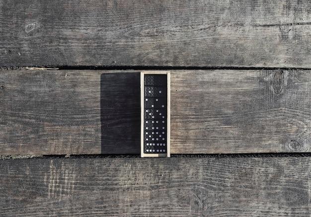 Cassetta di legno con pezzi di gioco del domino su vista dall'alto della scrivania in legno di legno invecchiato