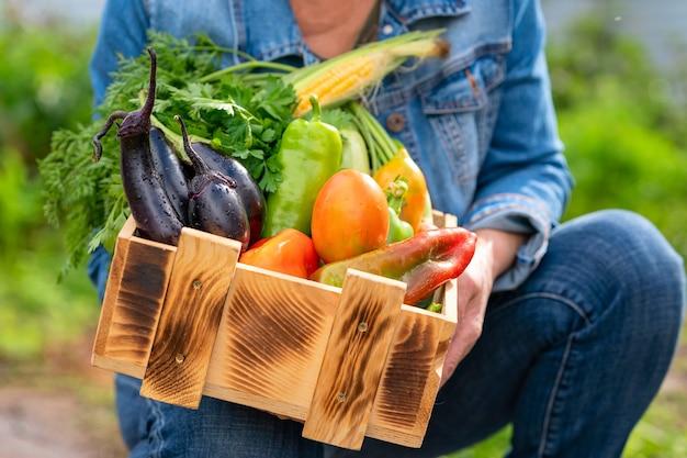 Una scatola di legno piena di verdure fresche fresche dell'orto