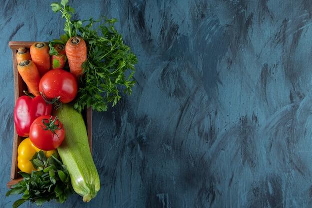 Scatola di legno di verdure fresche fresche su sfondo blu.