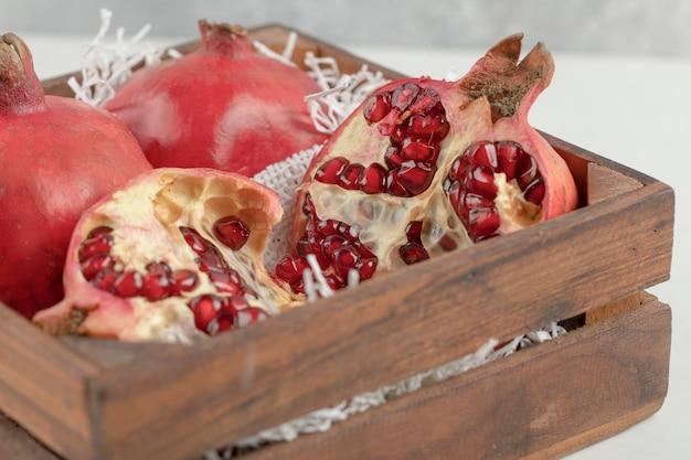Scatola di legno di melograni rossi freschi sulla tavola bianca.