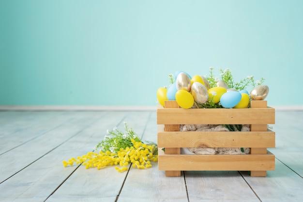 Scatola di legno con uova di pasqua blu, gialle e oro contro un muro blu