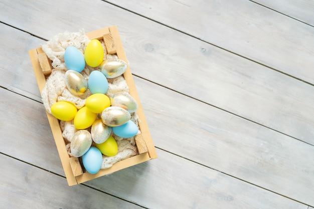 Scatola di legno con uova di pasqua blu, gialle e oro