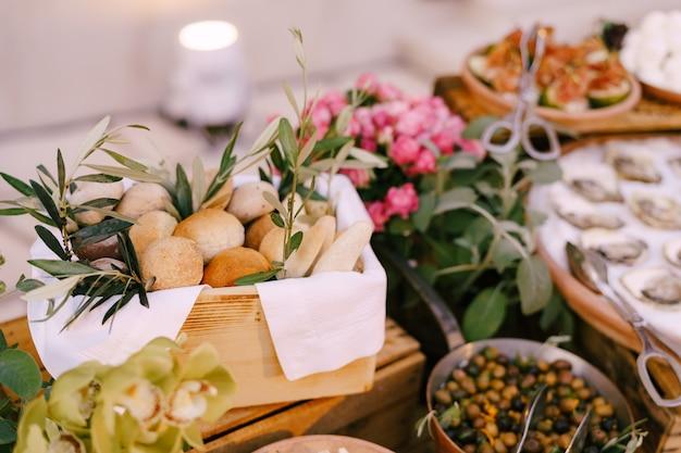 Scatola di legno con panini sullo sfondo di olive ripiene di ostriche e un mazzo di fiori