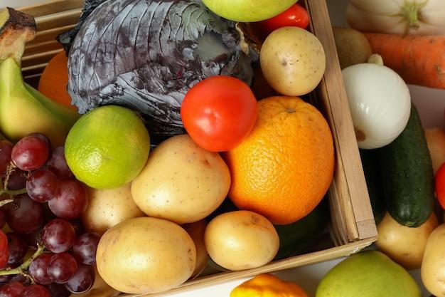 Scatola di legno con diverse verdure e frutta, vista dall'alto