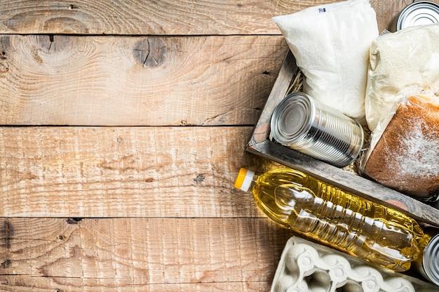Scatola di legno con cibo per donazioni, concetto di aiuto per la quarantena. olio, conserve, pasta, pane, zucchero, uova. fondo in legno. vista dall'alto. copia spazio.