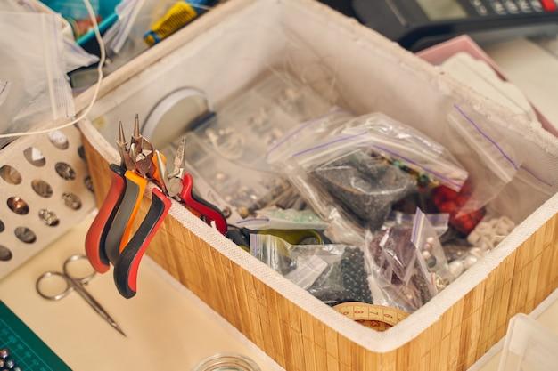 Scatola di legno con pinze per piegare il filo metallico con pinze a becco tondo per realizzare gioielli con chip e altre cose per hobby fatti a mano