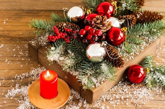 Scatola di legno con palline di natale rosse e rami, bacche e coni sul tavolo del villaggio con una candela di natale.