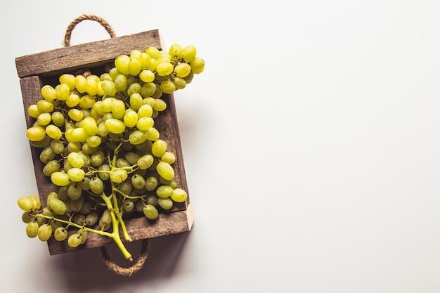 Scatola di legno con uve rosse isolato su sfondo bianco.