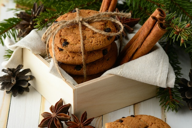 Scatola di legno con biscotti dolci al cioccolato composti da una stecca di cannella e rami aromatici di conifere.