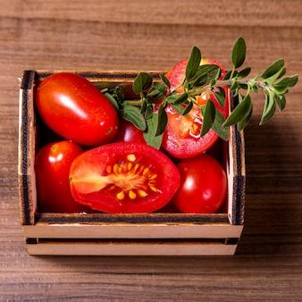 Scatola di legno con pomodori e rametto di origano.