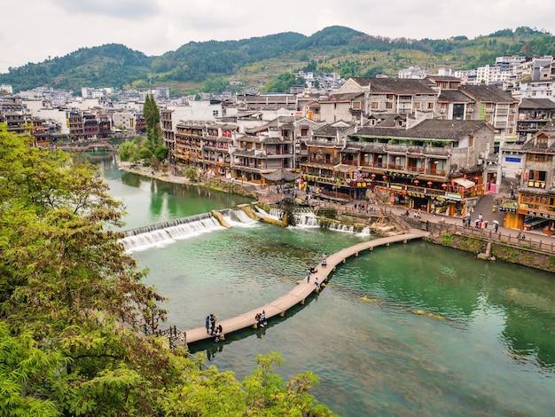 Ponte di legno e splendido scenario vecchio edificio della città antica di fenghuang.
