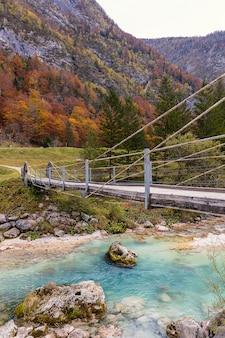Ponticello di legno sopra il chiaro fiume del turchese di soca in alpi slovene nella stagione di autunno