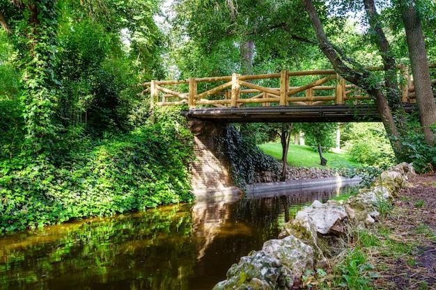 Ponte di legno su un piccolo ruscello nel parco pubblico del retiro, madrid.