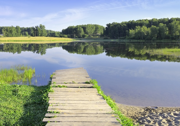 Ponti di legno sulla riva del lago una mattina limpida sulla superficie dell'acqua circondata da alberi