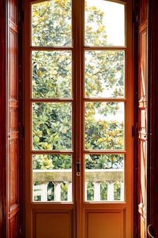 Una porta di legno marrone con vetri che si affaccia su un balcone con colonne bianche e un alto albero verde