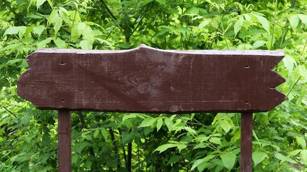 Cartello in legno marrone su uno sfondo di foglie verdi, cespugli e alberi in un parco o in una foresta. posto per il tuo testo o logo, pubblicità. copia spazio. segno vuoto, vuoto.