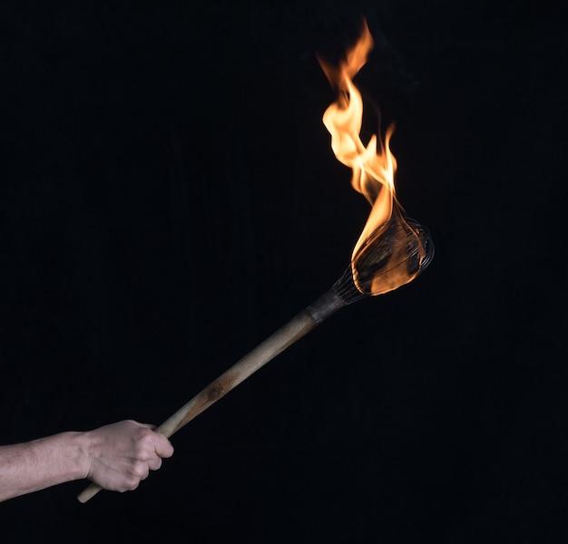 Torcia ardente in legno su sfondo nero