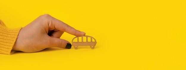 Autobus di legno in mano su sfondo giallo, concetto di trasporto, mock-up panoramico