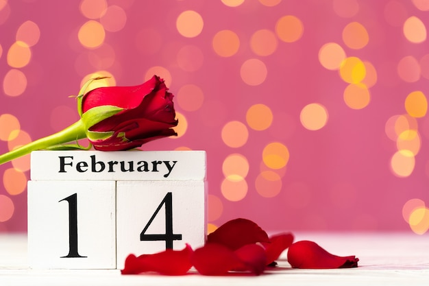 Calendario in legno 14 febbraio su sfondo rosa bokeh vista frontale