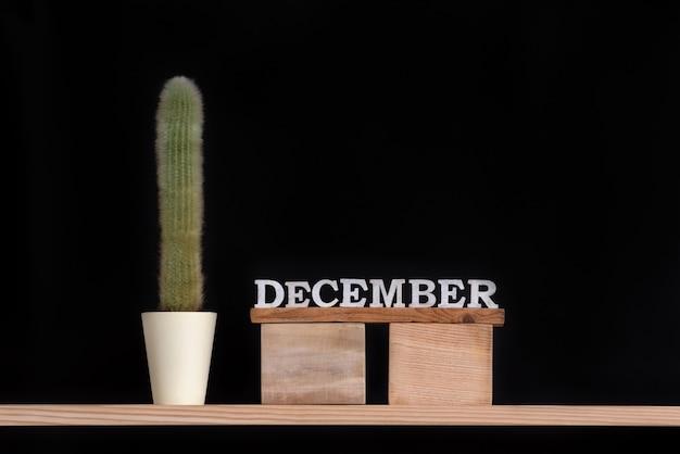 Calendario in legno di dicembre e cactus