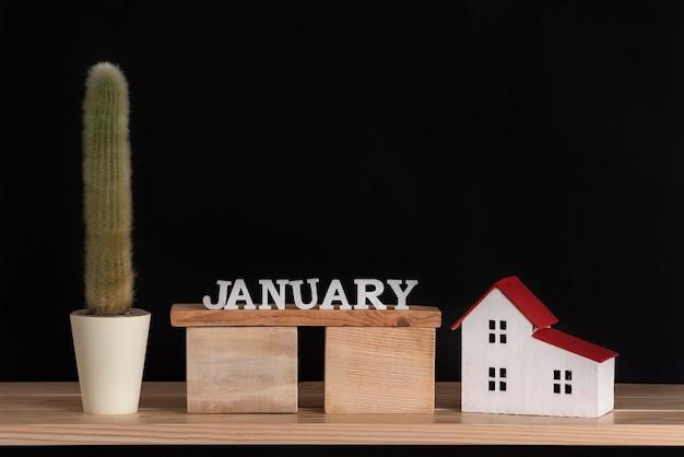 Calendario in legno di gennaio, cactus e modello di casa su fondo nero. copia spazio.